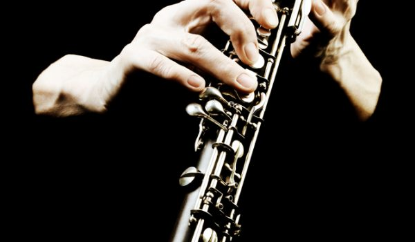 Oboe musical instrument of symphony orchestra. Oboist hands playing isolated on black. It's not clarinet, it's oboe! It is first instrument of classical orchestra.
